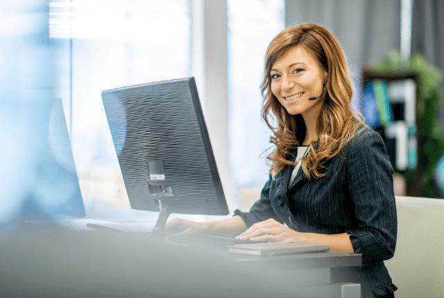 אישה במחשב עם אוזניות מחייכת